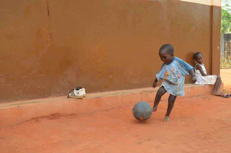 Kleiner Junge schießt mit Fußball